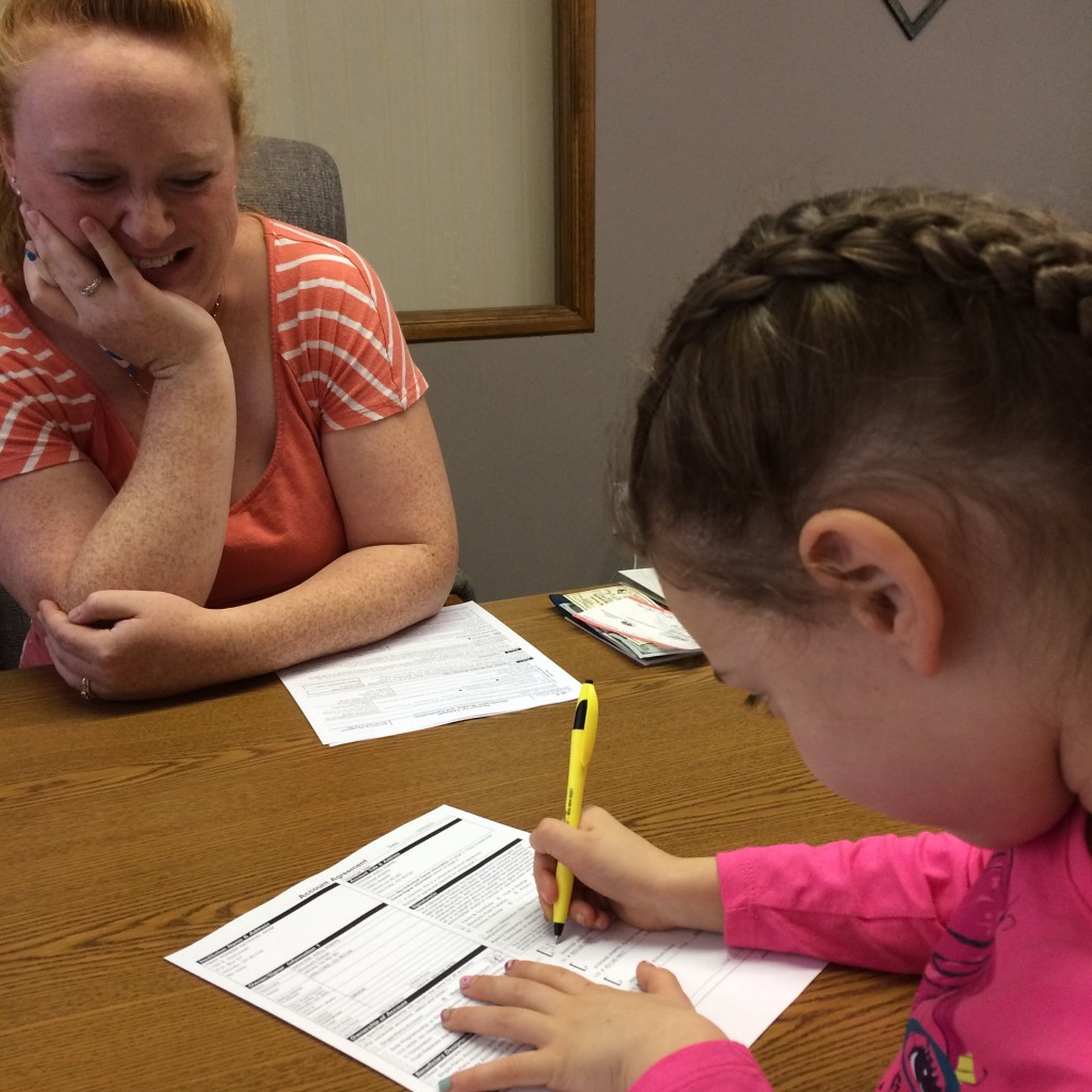 Signing her paperwork with our sweet friend, Katie